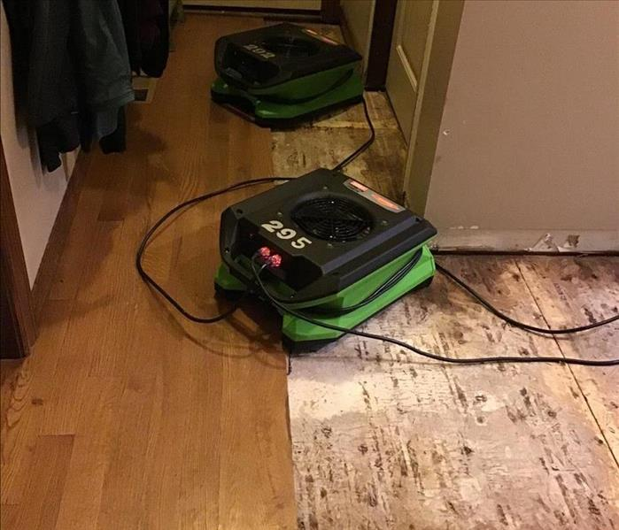 Warped flooring removed and air movers placed to dry